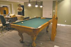 A pool table with hanging overhead lamps is centrepiece.
