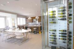 A tempered glass wine cooler in the kitchen adds to the gorgeous overall design.