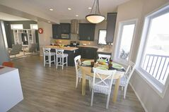 The kitchen features a mid-sized island, corner sink, dark cabinets and a spacious dining area next to a bay window.
