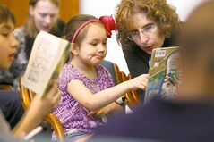 Claudia Sanderg, 6, reads with lawyer Brenda Silver.
