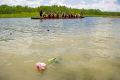 Paddlers threw flowers into the water during a ceremony at the 2014 River City Dragon Boat Festival at the Manitoba Water Ski Park on Lake Shirley Saturday afternoon.