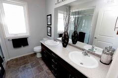 The master bathroom features a six-foot tempered glass shower and maple vanity.