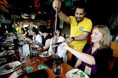Fabio Pena serves Maminha/tri-tip steak  to Eden Ramsay  during a visit to Carnaval Brazilian BBQ on the Little South America Exchange District food tour.