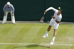 Milos Raonic of Canada a serves to Matthew Ebden of Australia during their first round match at the All England Lawn Tennis Championships in Wimbledon, London, Tuesday, June 24, 2014. (AP Photo/Ben Curtis)