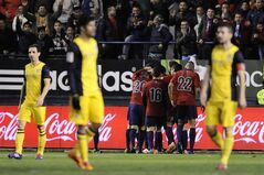 Osasuna's players celebrate their second goal after scoring against Atletico de Madrid, during their Spanish League soccer match, at El Sadar stadium in Pamplona, Spain, Sunday, Feb. 23, 2014. (AP Photo/Alvaro Barrientos)