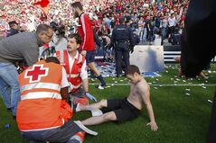 Osasuna's supporter lies on the pitch after one fence of the stadium was broken while people celebrated their team's, during their last Spanish League soccer match between Osasuna and Betis,, at El Sadar stadium, in Pamplona northern Spain, Sunday, May 18, 2014. (AP Photo/STR)