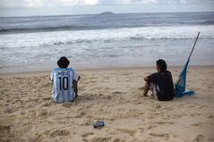Argentina soccer fans, one wearing a Lionel Messi soccer jersey, sit on Copacabana beach the morning after thier team was defeated by Germany at the World Cup final, in Rio de Janeiro, Brazil, Monday, July 14, 2014. (AP Photo/Rodrigo Abd)