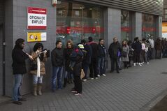People wait in line to enter an unemployment registry office in Madrid, Spain, Thursday, Jan. 23, 2014. Spain's sky-high unemployment rate remained stuck at 26 percent in the fourth quarter as the economy expanded but not enough to trigger job growth, according to a pair of government reports issued Thursday. The jobless rate for the October-December period rose to 26.03 percent from 25.98 percent in the previous quarter and the number of unemployed stood at a rounded 5.9 million people, Spain's National Statistics Agency said. The banner reads: