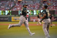 Oakland Athletics' Yoenis Cespedes, left, is congratulated by Alberto Callaspo after scoring on a single by Stephen Vogt during the second inning of a baseball game against the Los Angeles Angels, Monday, June 9, 2014, in Anaheim, Calif. (AP Photo/Mark J. Terrill)