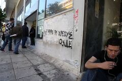 A young man smokes a cigarette as he waits outside Labor Force Employment Organization (OAED) with the graffiti reads in Greek ''Debt cancelation'' in Athens, April 11, 2013. THE CANADIAN PRESS/AP, Thanassis Stavrakis