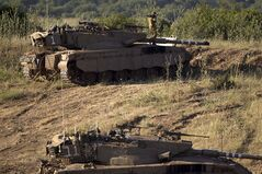 An Israeli soldier works on top of a tank in a position in the Israeli controlled Golan Heights, on the border with Syria, Tuesday, May 21, 2013. Israel's military chief has issued a stern warning to Syrian leader Bashar Assad after an Israeli military jeep came under fire from Syrian forces early Tuesday. Lt. Gen. Benny Gantz said on Tuesday that Israel will not allow the Golan Heights
