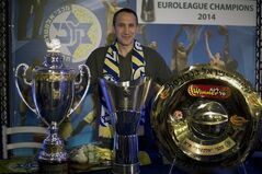 Maccabi Tel Aviv's head coach David Blatt poses for photographers with the Israeli cup, European club champions cup and the Israeli club champions trophy after a news conference in Tel Aviv, Israel,Thursday, June 12, 2014. David Blatt has stepped down as coach of European club champion Maccabi Tel Aviv to pursue a job in the NBA. Blatt told a news conference on Thursday he wanted to fulfil his