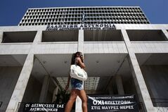 A pedestrian walks past the headquarters of the Greek Police in Athens, Wednesday, Sept. 5, 2012. Protest banners at the entrance of the building read: