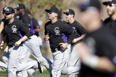 Colorado Rockies left fielder Carlos Gonzalez, center, jogs with teammates during a spring training baseball practice Wednesday, Feb. 26, 2014, in Scottsdale, Ariz. (AP Photo/ Gregory Bull)