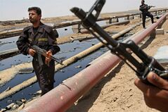 FILE - In this June 22, 2008 file photo, Iraqi police officers protecting oil installations secure an oil pipeline from the Rumailah refinery, north of Basra, Iraq. The turmoil in Iraq has thrown the OPEC member's ambitious plans to boost oil production into doubt, threatening to crimp its most vital economic lifeline. Northern oil fields imperiled by the militants' advance have been shut down, and companies have begun evacuating workers elsewhere in the country. Iraq's Kurdish minority has moved to solidify control over the northern oil-rich city of Kirkuk and other disputed areas, weakening Baghdad's claims to the energy riches buried beneath while bolstering the Kurds' aspirations of greater autonomy. (AP Photo/Nabil al-Jurani, File)