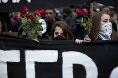 Masked protesters carry a banner and roses while marching in Sao Paulo, Brazil, Thursday, June 19, 2014. The protest in Sao Paulo, Brazil's biggest city that is hosting a World Cup match, was called by the Free Fare movement, the group that was behind the first protests last year that sparked roiling anti-government demonstrations across Brazil. (AP Photo/Eduardo Verdugo)
