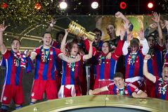 Bayern's Philipp Lahm holds the trophy as the team of FC Bayern Munich celebrates after winning the German Soccer Cup Final between FC Bayern Munich and Borussia Dortmund at the Olympic Stadium in Berlin, Germany, Saturday, May 17, 2014. (AP Photo/Gero Breloer)