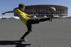 Lucas Zanatta, 10, plays with a soccer ball outside the National Stadium after visiting the official World Cup trophy on exhibit at the stadium in Brasilia, Brazil, Wednesday, May 28, 2014. Brasilia is one of the host cities for the 2014 World Cup in Brazil. (AP Photo/Eraldo Peres)