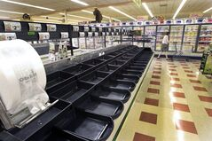 A customer walks by the empty produce isle Thursday July 24, 2014 at a Market Basket supermarket in Concord, N.H. A decades-long family feud, which brought about the ouster of Arthur T. Demoulas as CEO of the privately held company, led to a worker revolt, customer boycotts and empty shelves in the grocery chain's stores in Maine, Massachusetts and New Hampshire. More than 100 Massachusetts legislators and mayors, Massachusetts Attorney General Martha Coakley, and New Hampshire Gov. Maggie Hassan have publicly supported the employees. (AP Photo)