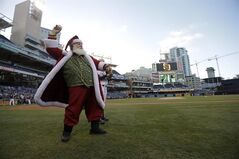 A man dressed as Santa Claus warms up before throwing out a ceremonial first pitch as the San Diego Padres prepared to play the Arizona Diamondbacks in a baseball game Wednesday, Sept. 3, 2014, in San Diego. (AP Photo/Gregory Bull)
