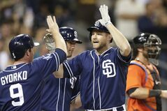 San Diego Padres' Chase Headley, right, is greeted at the plate by teammates Jedd Gyorko, left, and Seth Smith, center, after hitting a three-run home run while playing the Miami Marlins during the sixth inning of a baseball game Saturday, May 10, 2014, in San Diego. (AP Photo/Gregory Bull)