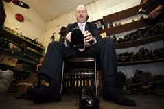 B.C. Finance Minister Mike de Jong tries on his budget day shoes after having the soles replaced at the Olde Towne Shoe Repair in Victoria, B.C. Monday, February 17, 2014. De Jong will table the provincial budget on Tuesday. THE CANADIAN PRESS/Chad Hipolito