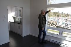 Dan Boot, designer and developer for Small Modern Living Inc., looks out from inside a 400 sq. ft. home at the Westbay Marina in Victoria, B.C. The modern looking home can fit into most backyards for under $100,000 and offers features such as granite counter tops, glass tiles, engineered wood flooring, high efficiency washer and dryer, a living room area, kitchen, bathroom and wall bed. THE CANADIAN PRESS/Chad Hipolito