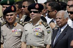 FILE - In this Friday, Sept. 20, 2013 file photo, Egypt's Defense Minister Gen. Abdel-Fattah el-Sissi, center, Egyptian Prime Minister Hazem el-Beblawi, right, and army's Chief of Staff Lt. Gen. Sedki Sobhi, left, attend the funeral of Giza Police Gen. Nabil Farrag in Cairo, Egypt. Egypt's interim prime minister Hazem el-Beblawi announced Monday the resignation of his Cabinet, a surprise move that could be designed in part to pave the way for the nation's military chief to leave his defense minister's post to run for president. El-Beblawi has often been derided in the media for his perceived indecisiveness and inability to introduce effective remedies to the country's economic woes. (AP Photo/Hassan Ammar, File)