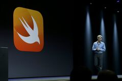 Apple senior vice president of Software Engineering Craig Federighi walks next to a symbol for Swift, a new programming language, while speaking at the Apple Worldwide Developers Conference in San Francisco, Monday, June 2, 2014. (AP Photo/Jeff Chiu)