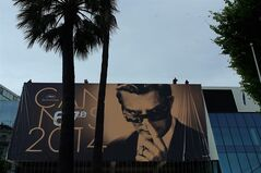 Workers place a banner depicting Marcello Mastroianni from Federico Fellini's film 8� on the Palais during preparations for the 67th international film festival, Cannes, southern France, Monday, May 12, 2014. The festival runs from May 14 to May 25. (AP Photo/Thibault Camus)