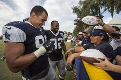 Dallas Cowboys defensive end Tyrone Crawford (98), left, and teammate defensive end Jeremy Mincey (92) sign autographs at the end of practice at NFL football training camp, Wednesday, July 30, 2014, in Oxnard, Calif. (AP Photo/Ringo H.W. Chiu)