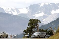 A family stops at a pull off on Trail Ridge Road, inside Rocky Mountain National Park just west of Estes Park, Colo., Monday, July 14, 2014. Two fatal lightning strikes on consecutive days the previous weekend on the high-altitude road pinpoint dangers not always apparent to visitors to the exposed high country of the park. Afternoon storms visible miles away arrive overhead suddenly. (AP Photo/Brennan Linsley)