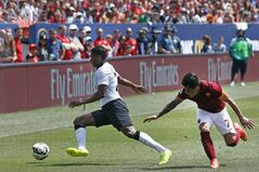 Manchester United's Antonio Valencia, left, evades coverage by AS Roma's Juan Iturbe during the first half of an exhibition soccer match against at Mile High Stadium, in Denver, Saturday, July 26, 2014. (AP Photo/Brennan Linsley)
