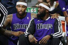 After falling into foul trouble, Sacramento Kings center DeMarcus Cousins, left, talks with forward Reggie Evans in the first half of an NBA basketball game against the Denver Nuggets in Denver, Sunday, Feb. 23, 2014. (AP Photo/David Zalubowski)