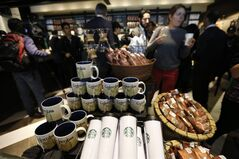 Journalists tour the first Starbucks the day before its public opening in Bogota, Colombia, Wednesday, July 16, 2014. The three-floor coffee house in Bogota is the first of 50 that the Seattle-based company plans to open here in the next five years. (AP Photo/Fernando Vergara)