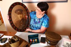 This handout photo of Diana Snow was taken in St. John's, N.L., on Sun. Aug. 10, 2014, with a portrait of her grandfather, William Newell, one of the First 500 volunteers who signed up to fight in the First World War when Newfoundland was still a British dominion. On the table in front of her is what remains of her grandfather's original military kit. THE CANADIAN PRESS/Mike Wert.