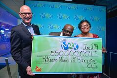 Ontario Lottery and Gaming Corp. Senior Vice President of Lottery Greg McKenzie presents Brampton resident Hakeem Nosiru and his wife Abiola with a cheque for $50,000,004 at the OLG Prize Centre in Toronto, Monday, June 2, 2014. A Toronto-area couple endured a roller-coaster ride of emotions when a lottery ticket worth $50 million went missing only to be found and returned by a person at their church. THE CANADIAN PRESS/HO-OLG-Shan Qiao