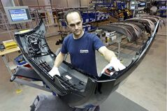 Assembler Christian Baumann carries a front car bumper at a Magna plant in Meerane, Germany, on April 24, 2013. THE CANADIAN PRESS/AP, Jens Meyer