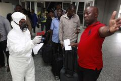 Nigerian port health official uses a thermometer on a passengers at the arrivals hall of the Lagos airport in Nigeria on Aug. 6, 2014. THE CANADIAN PRESS/AP, Sunday Alamba