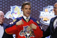 Aaron Ekblad pulls on a Florida Panthers jersey after being chosen first overall in the NHL hockey draft, Friday, June 27, 2014, in Philadelphia.The Panthers and Ekblad have agreed on a three-year entry-level contract THE CANADIAN PRESS/AP/Matt Slocum