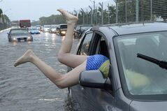 A woman gets gets back in her car in flood water on Lakeshore West during a storm in Toronto on Monday, July 8, 2013. Last year, Calgary and Toronto homeowners and businesses were hit with severe flooding that was aggravated by sealed topsoil that could not absorb the sudden influx of water, costing billions in damages. THE CANADIAN PRESS/Frank Gunn