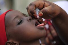 A health official administers a polio vaccine to a child in Kawo Kano, Nigeria, April 13, 2014. THE CANADIAN PRESS/AP, Sunday Alamba