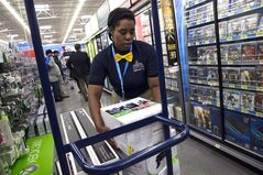Tracey Anderson re-stocks X-Box sets at a Wal-Mart in Washington on Dec. 4, 2013. THE CANADIAN PRESS/AP, Jacquelyn Martin