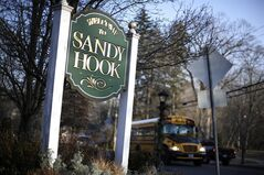 A bus drives past a sign reading Welcome to Sandy Hook, Wednesday, Dec. 4, 2013, in Newtown, Conn. The 911 calls from the Sandy Hook Elementary School shootings released Wednesday show town dispatchers urged panicked callers to take cover, mobilized help and asked about the welfare of the children as the boom of gunfire could be heard at times in the background. The recordings are released under court order after a legal challenge from The Associated Press. (AP Photo/Jessica Hill)
