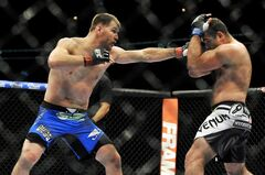 Stipe Miocic, left, punches Gabriel Gonzaga, right, during the heavyweight bout of a UFC mixed martial arts match in Chicago, Saturday, Jan. 25, 2014. (AP Photo/Paul Beaty)