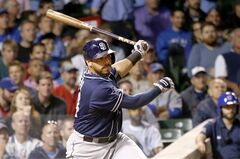 San Diego Padres' Rene Rivera hits a two-run single off Chicago Cubs relief pitcher Brian Schlitter, scoring Will Venable and Jake Goebbert, during the sixth inning of a baseball game on Thursday, July 24, 2014, in Chicago. (AP Photo/Charles Rex Arbogast)