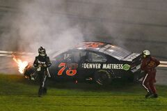 Martin Truex Jr., left, walks away from his car after he was involved in a multi-car crash on the last lap of the second of two NASCAR Sprint Cup qualifying auto races at Daytona International Speedway in Daytona Beach, Fla., Thursday, Feb. 20, 2014. (AP Photo/John Raoux)