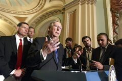Senate Minority Leader Mitch McConnell, R-Ky., joined by Sen. John Barrasso, R-Wyo., left, and Sen. John Thune, R-S.D., rear left, speaks to reporters after a Republican caucus meeting, at the Capitol in Washington, Tuesday, May 6, 2014. (AP Photo/J. Scott Applewhite)