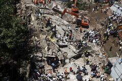 Rescue workers look for survivors and clear debris at the site of a building that collapsed in Mumbai, India, Friday, Sept. 27, 2013. The apartment building collapsed in India's financial capital of Mumbai early Friday, killing people and sending rescuers racing to reach dozens of people trapped in the rubble. (AP Photo/Rajanish Kakade)