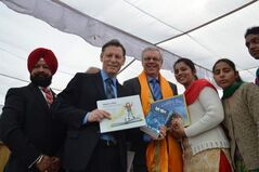 Premier Greg Selinger (centre) with University of Winnipeg's Terry Duguid  (left) and the university's student recruiting representative Kuljit Bhattal (far left). They're presenting books from Winnipeg to girls at a new library in Bhanohar.